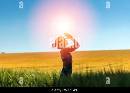 woman standing in a field meditating with sun in the sky, yoga pose. - Stock Image