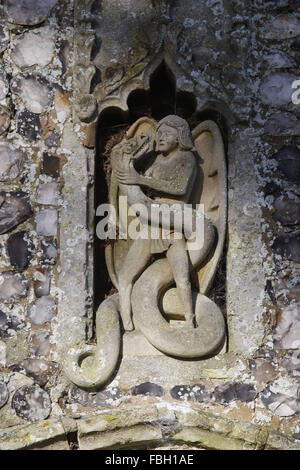 Carving of Archangel Michael fighting the serpent, St Michael's Church, Irstead, Norfolk - Stock Image