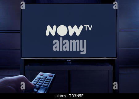 A man points a TV remote at the television which displays the logo for the Now TV on demand video streaming service (Editorial use only). - Stock Image