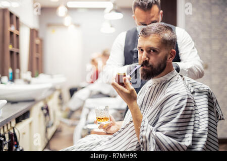 Handsome hipster man client visiting haidresser and hairstylist in barber shop, smoking a pipe. - Stock Image