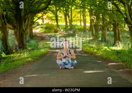 woman sitting crossed legged in the middle of a country road meditating practicing yoga. - Stock Image