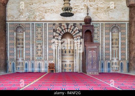 Colorful decorated marble wall with engraved Mihrab (niche) and wooden Minbar (Platform) at the Mosque of Al Nasir Mohammad Ibn Qalawun, Cairo - Stock Image