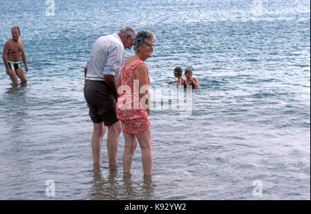 elderly couple wading in the sea - Stock Image