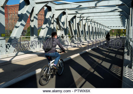 A cyclist travels over the former rail/road Ashton Avenue Bridge, now a guided busway/cycle & pedestrian route. Bristol, UK. - Stock Image