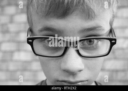 Black and white macro shot of upset preteen boy wearing glasses - Stock Image