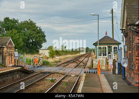 Signalman dressed in orange high visibility overalls manually operating level crossing gates at the rural Lincolnshire station of Swinderby - Stock Image