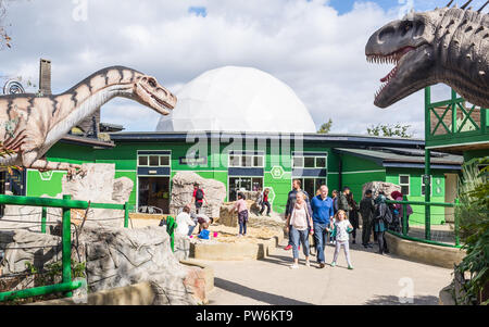 Gulliver's Dinosaur & Farm Park, Lost World - Milton Keynes, UK. Entrance of the park with people visiting and big dinosaurs replicas - Stock Image