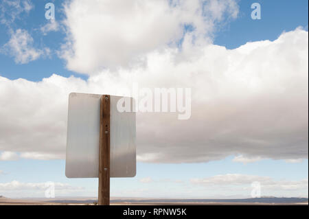 Back of road sign against blue sky and clouds - Stock Image