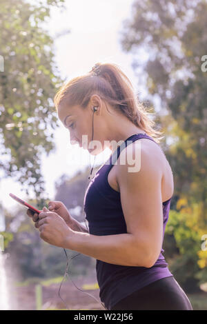 vertical photo of an attractive blonde sports woman checking her phone app before workout outdoors at park, fitness accessories - Stock Image