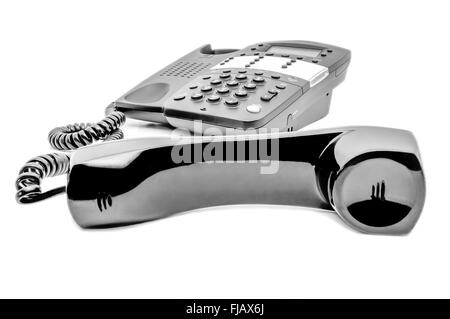 A black business telephone with the receiver off of the hook on a white background. - Stock Image