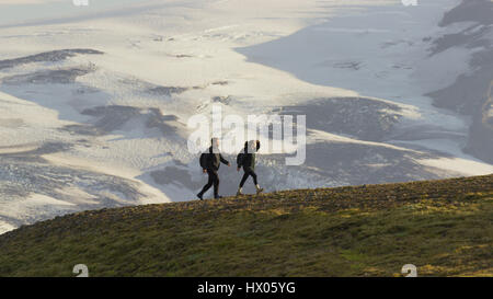 High angle view of hikers walking on grassy hilltop over snowy remote landscape - Stock Image