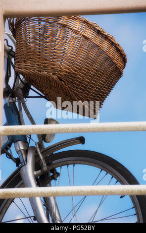 Bike with a basket parked by railings in Scheveningen, the Netherlands - Stock Image