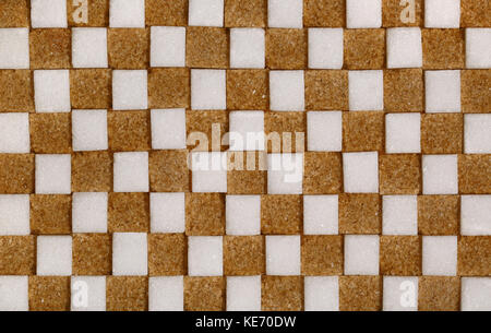 Brown and white sugar cubes making a chequered background - Stock Image