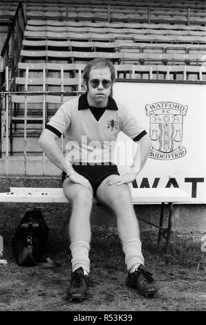 Elton John, just back from a tour of America, wants to be a director of Watford FC. He has always been a fan, and has just been made a vice president. Pictured at Watford to meet and train with the players to keep fit. Pictured, Elton John a bit puffed, relaxes during training. 7th November 1973. - Stock Image