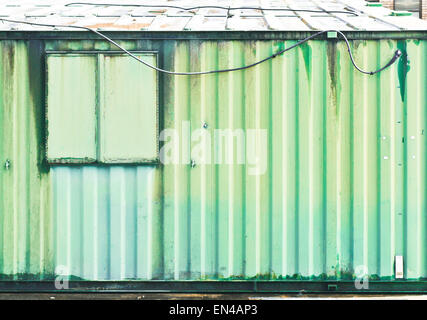 Rusty green corrugated metal on the exterior of an industrial building - Stock Image