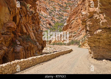 S-curve gravel road carved into orange colored rocky canyon - Stock Image