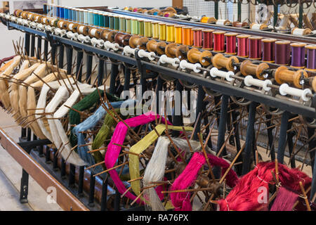 Whitchurch Silk Mill in Hampshire, UK. Interior of the museum with colourful silk yarns wound onto reels or bobbins. - Stock Image
