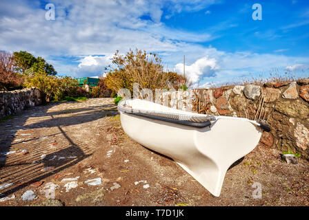 White fiberglass boat ashore on a soil walkway path on a sunny day - Stock Image