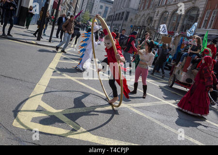 Climate Change protesting acrobats with Extinction Rebellion block central London and simultaneously stop traffic across the capital including Marble Arch, Piccadilly Circus, Waterloo Bridge and roads around Parliament Square, on 15th April 2019, in London, England. - Stock Image