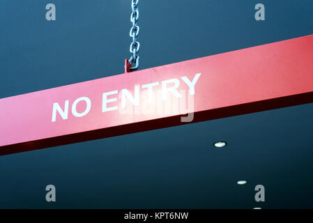 White text no entry sign on a red background hanging from a chain - Stock Image