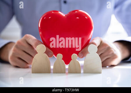 Person's hand protecting red heart with family figures - Stock Image