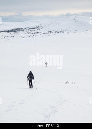 two men  with heavy packs snowshoeing away from camera through a   winter mountain landscape - Stock Image
