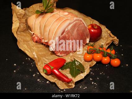 Rolled joint of raw Pork on Black background landscape. - Stock Image