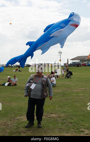 Portsmouth, UK. 15th August 2015. A kite handler walks away from the large shark kite he has just flown at the International - Stock Image