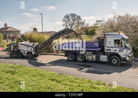 Presteigne, Powys, Wales, UK. A cold planer or milling machine removing the old road surface before new tarmac or asphalt is laid - Stock Image