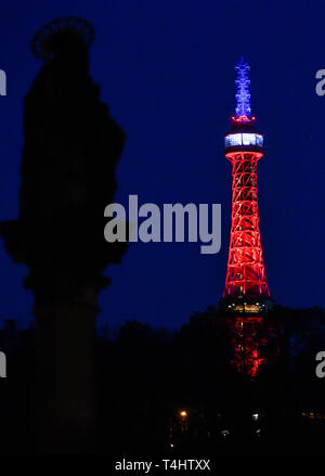 Prague, Czech Republic. 16th Apr, 2019. The lookout tower on Petrin hill in Prague centre was lit in the French national colours, red, blue and white, today, on Tuesday, April 20, 2019, in memory of the yesterday's fire-damaged Notre-Dame Cathedral in Paris. Credit: Vit Simanek/CTK Photo/Alamy Live News - Stock Image