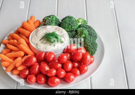 Homemade buttermilk ranch salad dressing with dill served with fresh vegetables, cherry tomatoes, baby carrots and broccoli, over a rustic white woode - Stock Image