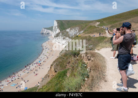 Lulworth, Dorset, UK. 23rd June 2018. People take photos of the view as of tourists visit the coast and beach at Durdle Door on the Dorset coast, near Lulworth Cove on a hot sunny day in June. Thomas Faull/Alamy Live News - Stock Image