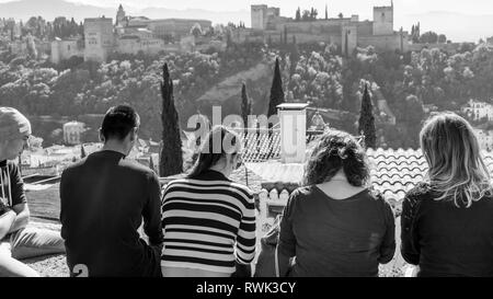 Tourists sitting with a view of the Alhambra; Granada, Andalusia, Spain - Stock Image