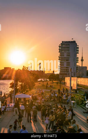 sunset at riverside Spree, Berlin wall, live band, living levels skyscraper, Friedrichshain, Berlin, Germany - Stock Image