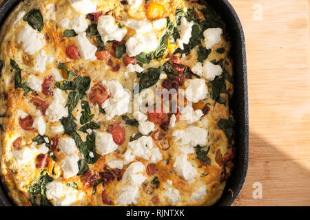 A freshly cooked frittata made with beaten eggs, goats cheese tomato, fresh basil. its still hot in the frying pan used to cook it - Stock Image