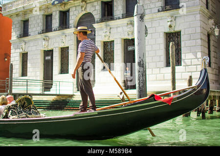 A singing gondola driver whistling on the gorgeous Grande Canal in Venice, Italy, Europe near rialto bridge - Stock Image
