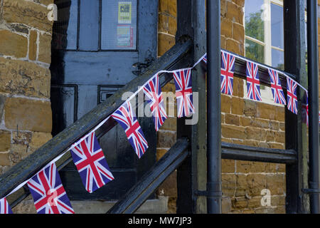 A row of small Union Jack flags strung along a wooden handrail outside a village pub; Great Brington, Northamptonshire, UK - Stock Image