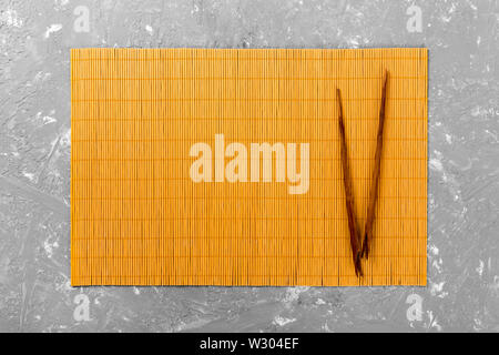 two sushi chopsticks with empty bamboo mat or wood plate on cement Background Top view with copy space. empty asian food background. - Stock Image