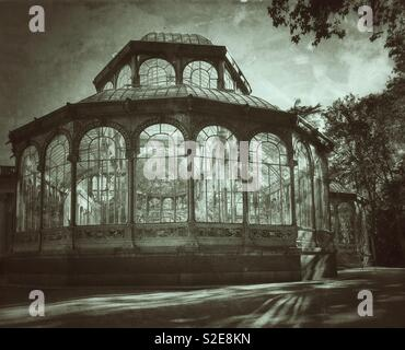 An antique and retro effect image of the famous Palacio de Cristal (Crystal Palace) in Beun Retiro Park in Madrid, Spain. No people present which adds to the spooky or sinister effect. Photo © -CH. - Stock Image