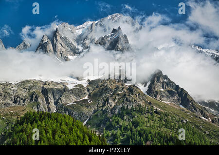 clouds over the top of the mountains of Mont Blanc Group Aosta Valley in spring season with blue sky in background - Stock Image