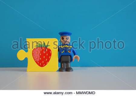 Playtive Junior postman figure standing next to a puzzle piece with strawberry illustration - Stock Image