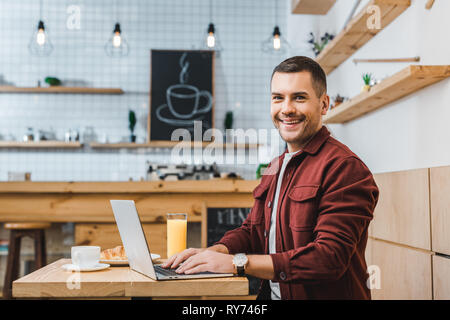 handsome freelancer sitting at table with laptop and smiling in coffee house - Stock Image