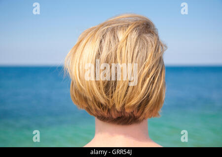 Blond woman gazing at the sea - Stock Image