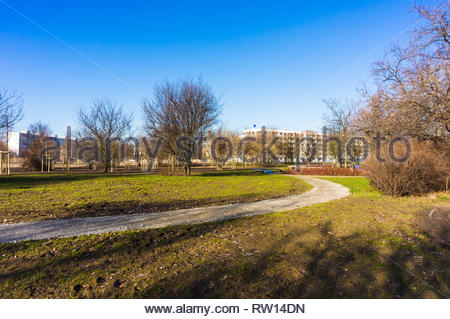 Poznan, Poland - February 16, 2019: Footpath along green grass leading to apartment blocks at a park. - Stock Image