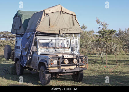 Old Land Rover Defender 110  Parked in a National Park Kenya. Roof tents pitched - Stock Image