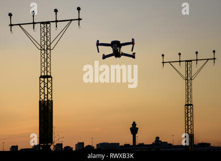 Unmanned drone flying near runway at airport in between approaching runway lighting at sunset. - Stock Image