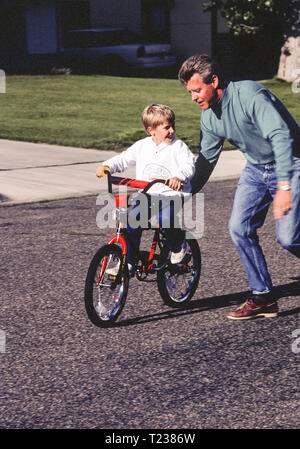 Father Teaching Son How to Ride a Two Wheel Bike, 1993. USA - Stock Image