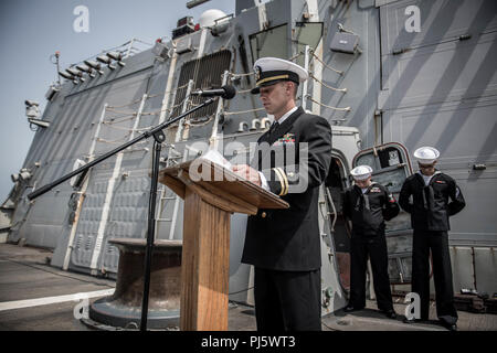 180825-N-UX013-1034 U.S. 5TH FLEET AREA OF OPERATIONS (Aug. 25, 2018) Lt. Cmdr. (Sel) Micky Weikel, chaplain of the guided-missile destroyer USS Jason Dunham (DDG 109), delivers a prayer during a memorial ceremony at sea for Ensign Sarah Mitchell. Dunham is deployed to the U.S. 5th Fleet area of operations in support of naval operations to ensure maritime stability and security in the Central Region, connecting the Mediterranean and the Pacific through the western Indian Ocean and three strategic choke points. (U.S. Navy photo by Mass Communication Specialist 3rd Class Jonathan Clay/Released) - Stock Image