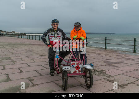 Penzance, Cornwall, UK. 24th November 2018. Perranporth based surfing chefs Pegleg Bennett ( who only has one leg)  and John Hudson just hours before completing their latest adventure - a charity bike ride from John O'Groats to Lands End, with their motto of '4 Wheels, 3 Legs, 2 Idiots, 1 Bike' Credit: Simon Maycock/Alamy Live News - Stock Image