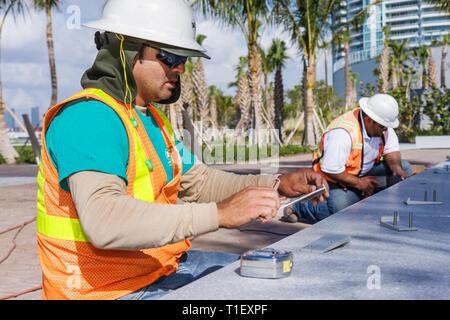 Miami Beach Florida South Pointe Park public park renovation Hispanic man men worker job tape measure hard hat reflective vest s - Stock Image